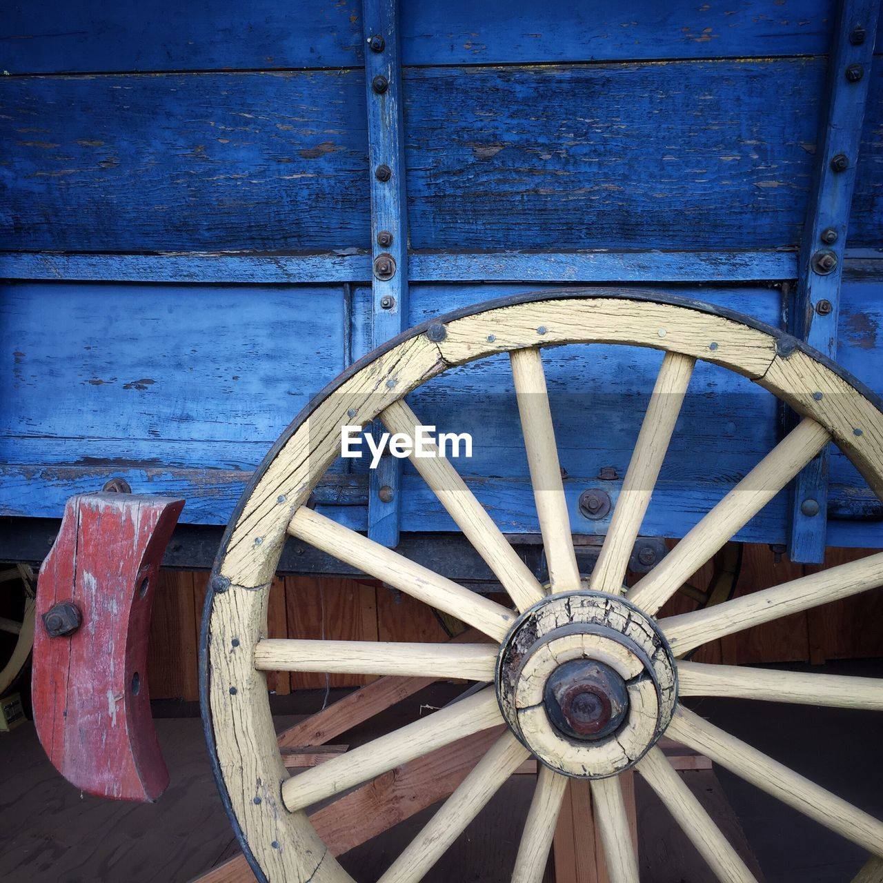 wood - material, wheel, no people, wagon wheel, day, transportation, close-up, circle, blue, outdoors, shape, old, geometric shape, cart, architecture, wall - building feature, design, pattern, weathered