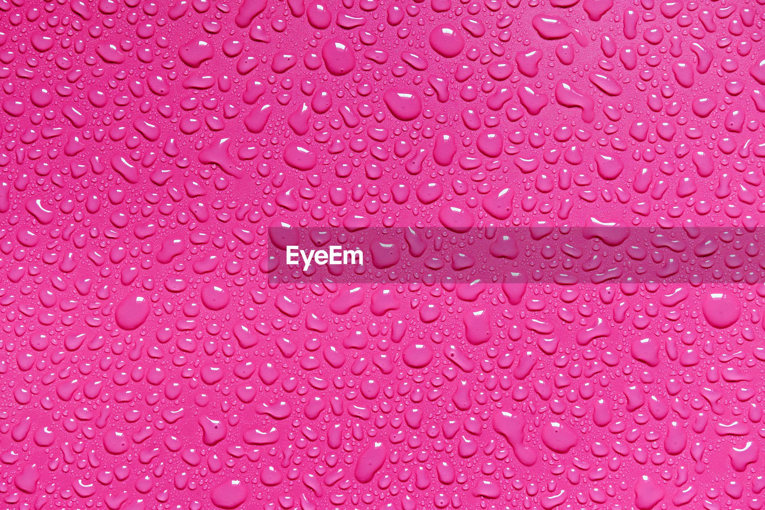 Full frame shot of raindrops on pink surface
