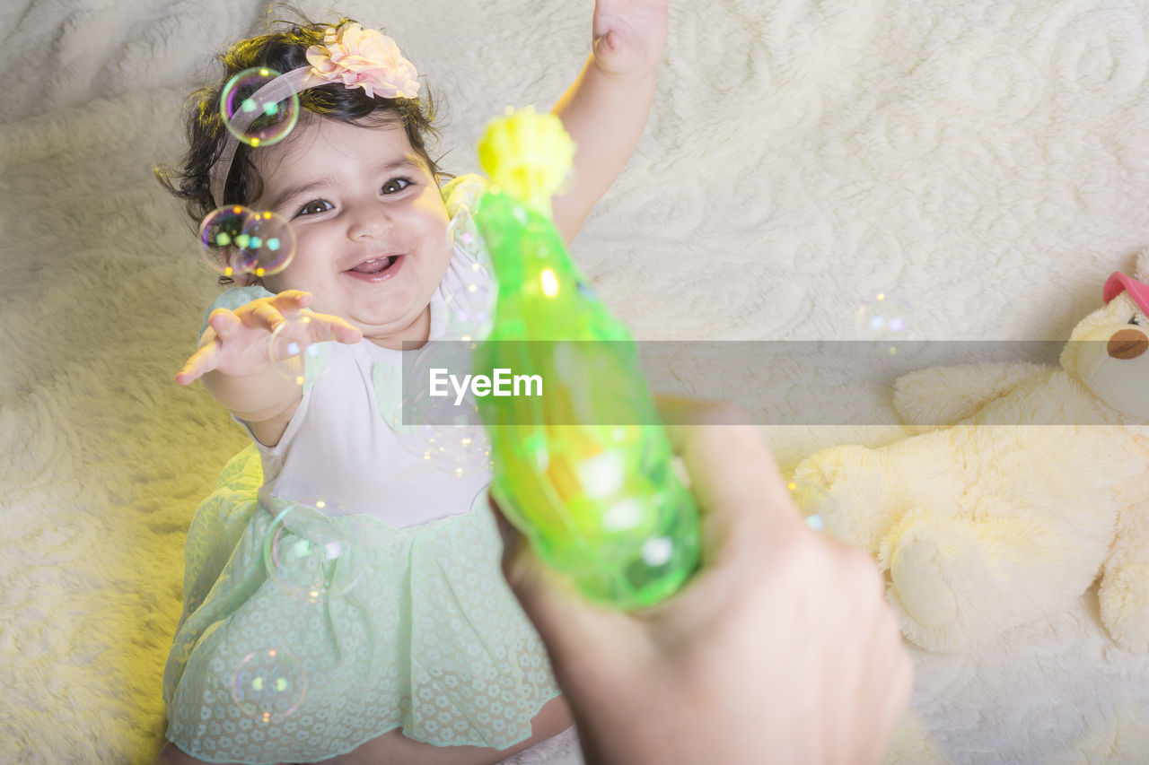 Cropped Hand Of Person Making Bubbles With Wand With Baby Girl Enjoying