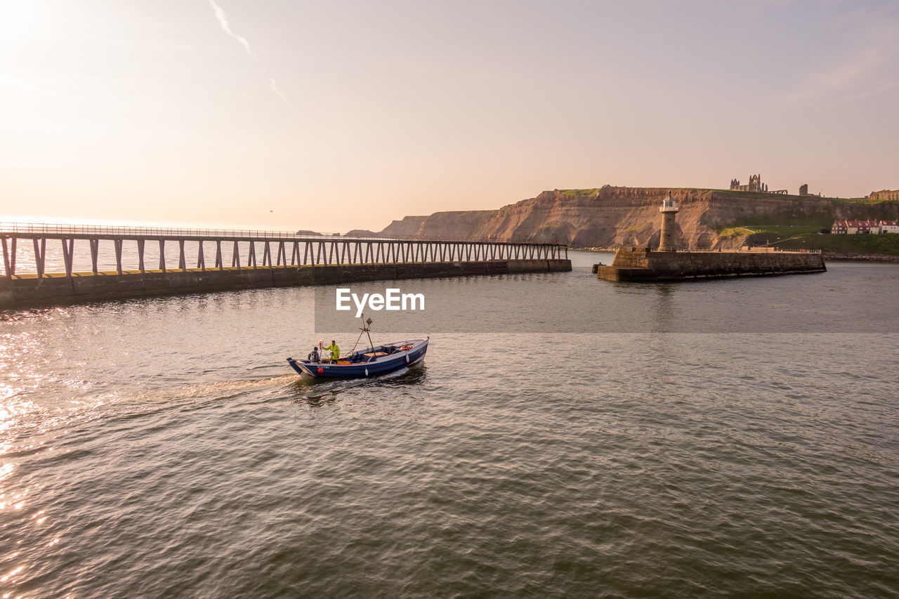 nautical vessel, water, transportation, mode of transportation, sky, waterfront, river, nature, real people, built structure, bridge - man made structure, bridge, architecture, sunset, travel, beauty in nature, men, scenics - nature, outdoors