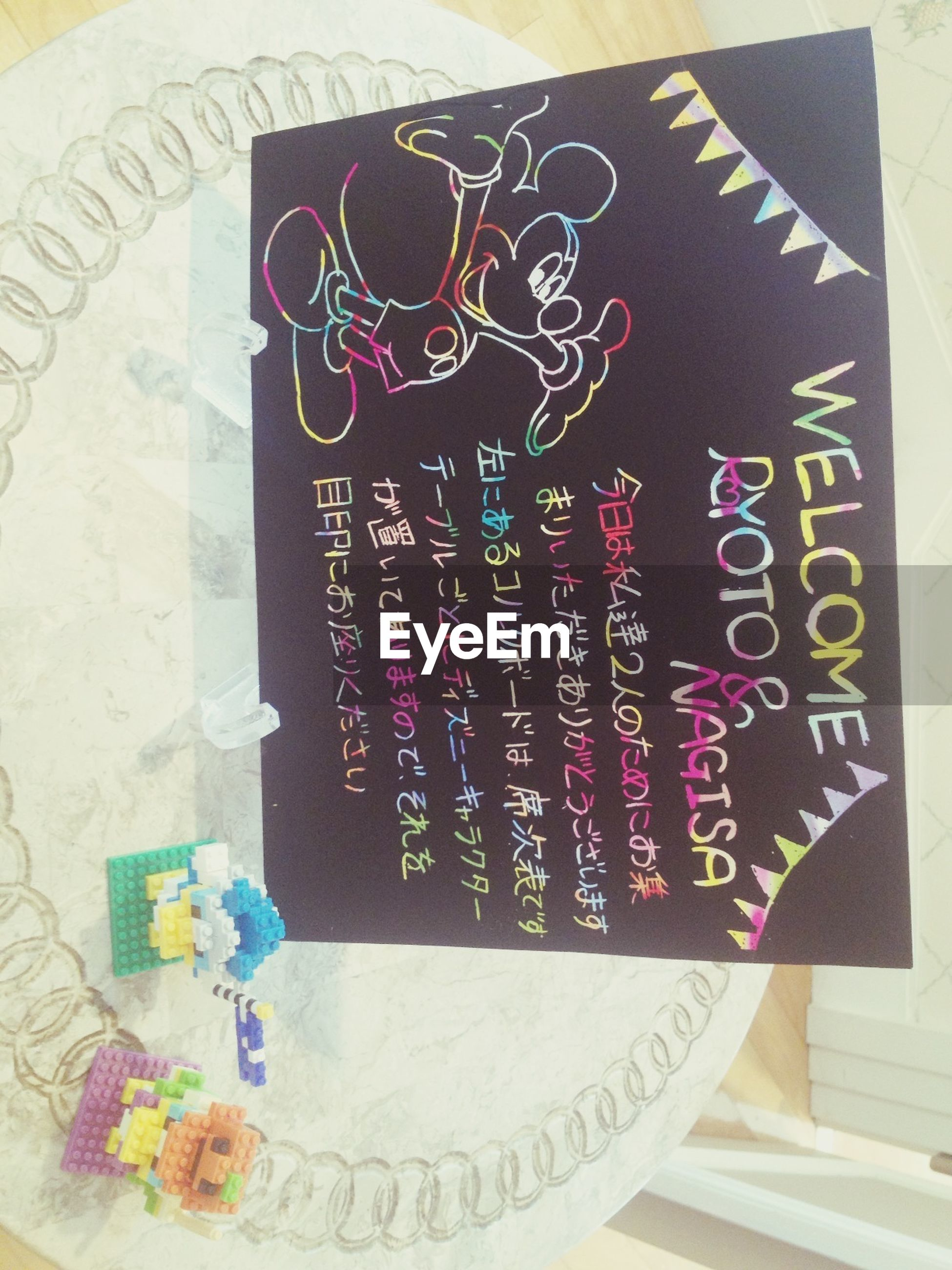 text, indoors, western script, communication, creativity, art and craft, art, paper, close-up, non-western script, table, high angle view, still life, message, multi colored, no people, handwriting, variation, craft, information