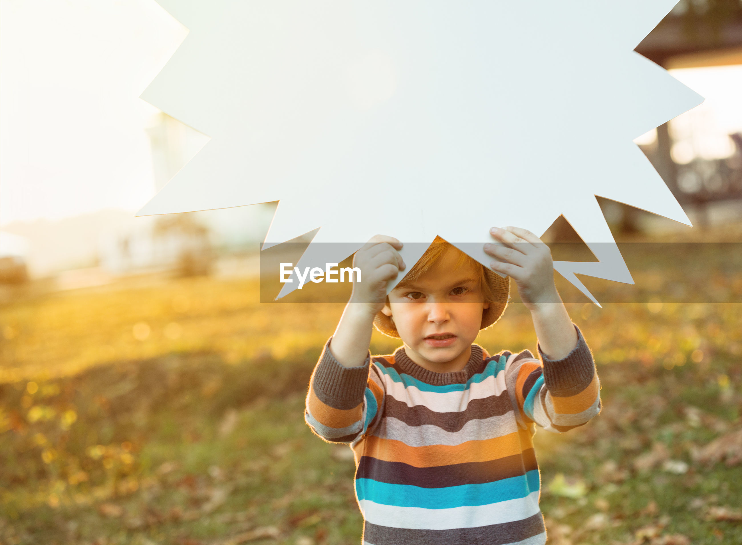 Portrait of boy holding speech bubble on field during sunset