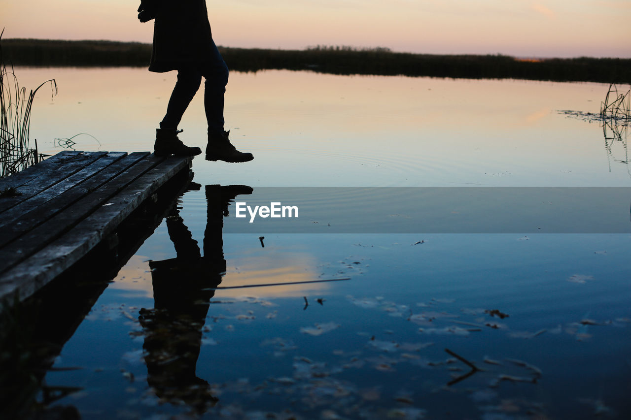 Person Stepping On Lake At Dusk