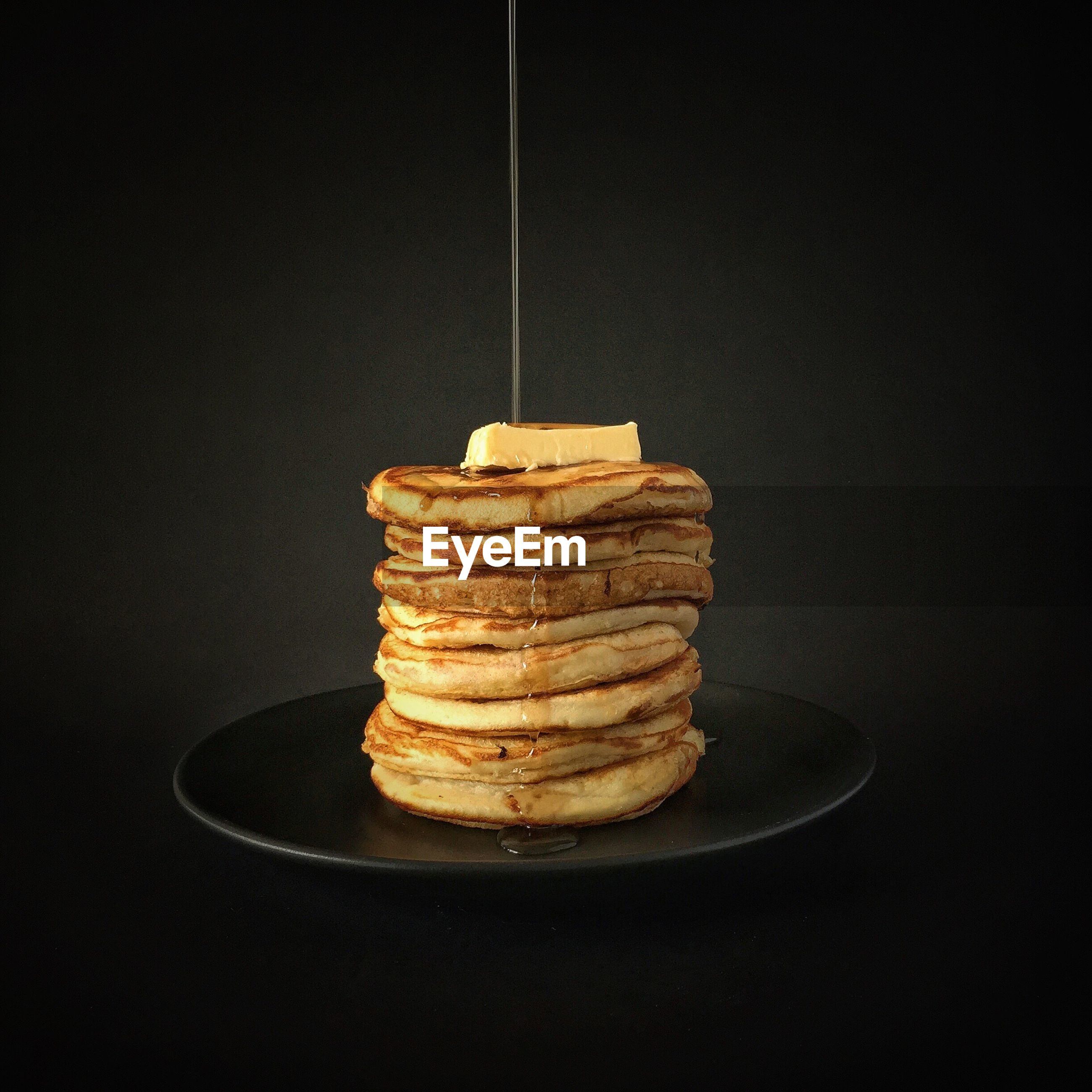Close-up of maple syrup flowing over pancakes