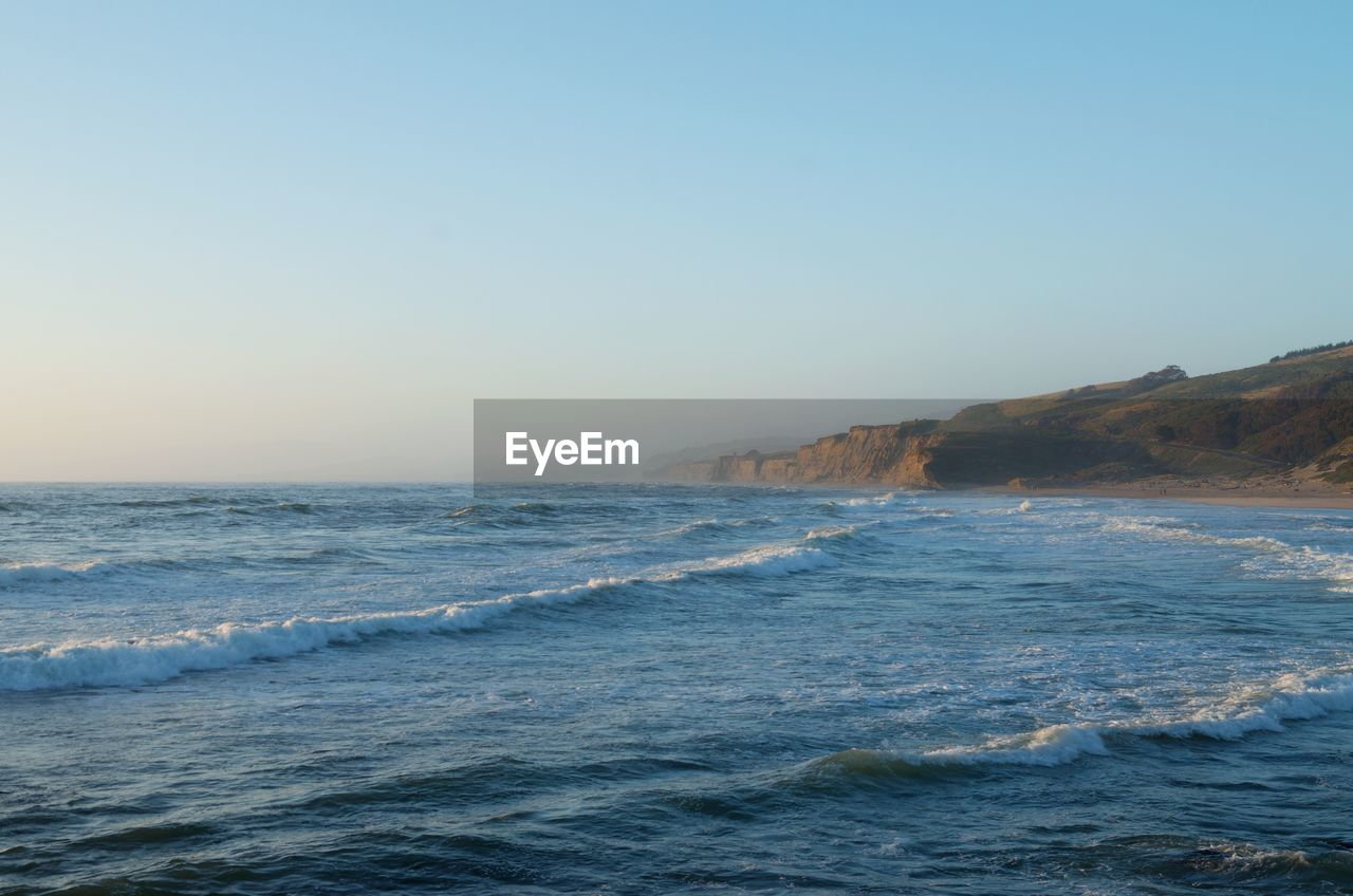 sea, water, sky, beauty in nature, scenics - nature, motion, wave, clear sky, copy space, nature, sport, waterfront, horizon, aquatic sport, land, blue, no people, outdoors, horizon over water, power in nature, flowing water