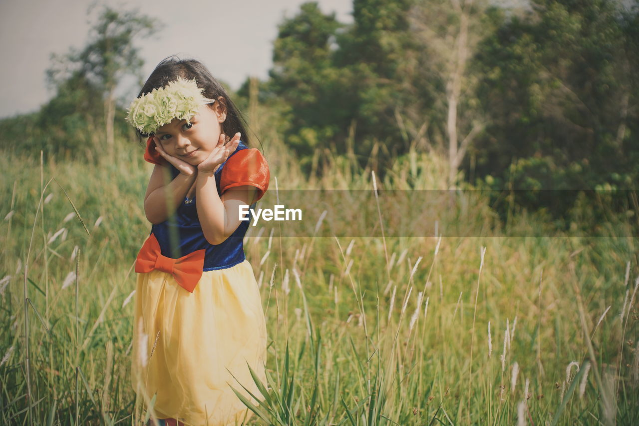 Portrait Of Cute Girl Wearing Flowers While Standing On Grassy Field