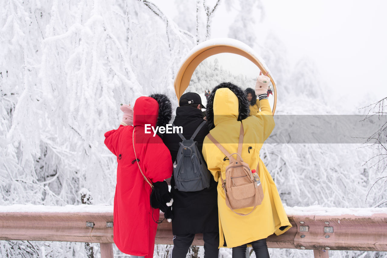 winter, cold temperature, clothing, snow, real people, rear view, women, togetherness, two people, lifestyles, warm clothing, people, nature, yellow, leisure activity, three quarter length, bonding, day, backpack, outdoors, hood - clothing, couple - relationship