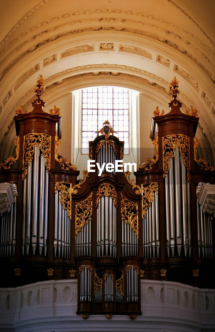 Low angle view of pipe organ in old church