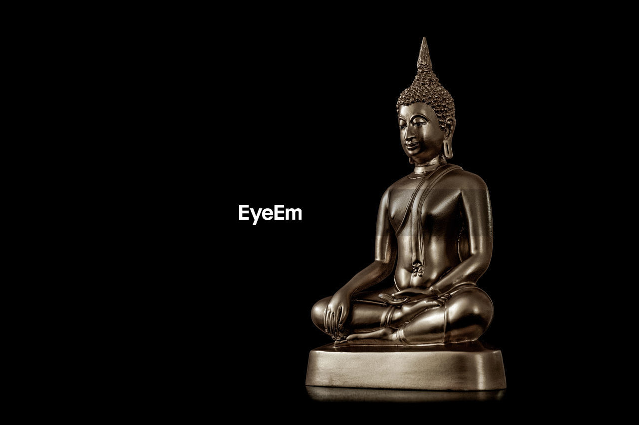 Buddha statue against black background
