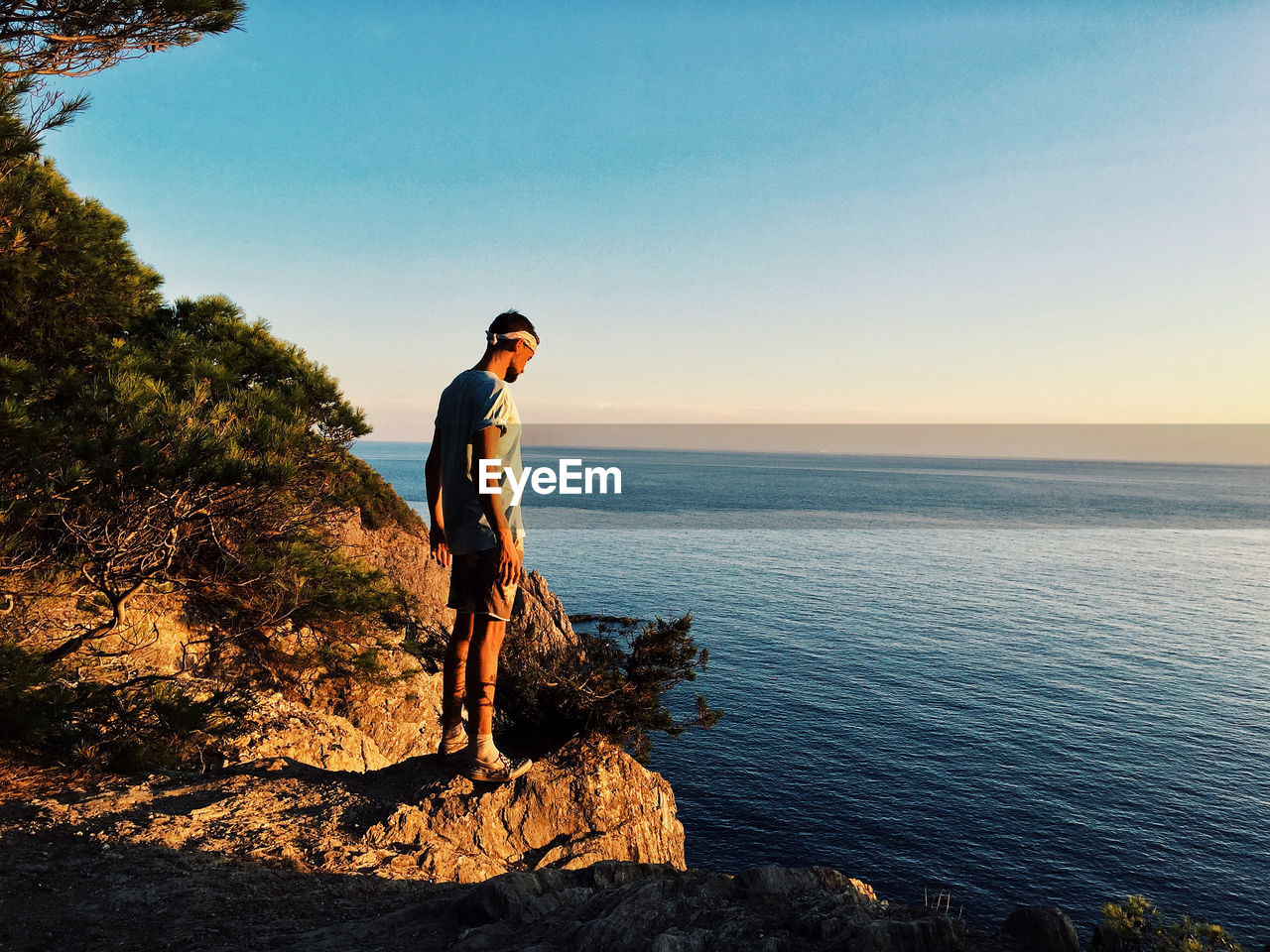 sky, sea, scenics - nature, real people, one person, lifestyles, rock - object, beauty in nature, rock, leisure activity, water, young adult, solid, standing, full length, young men, nature, tranquility, side view, horizon over water, outdoors