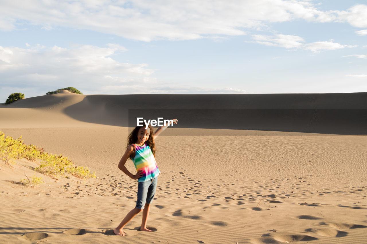 Full Length Of Girl Posing On Sand At Beach Against Sky
