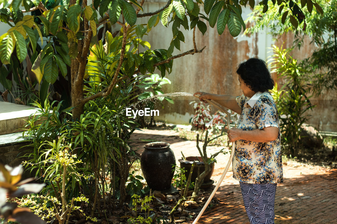 Woman watering plants and trees in yard