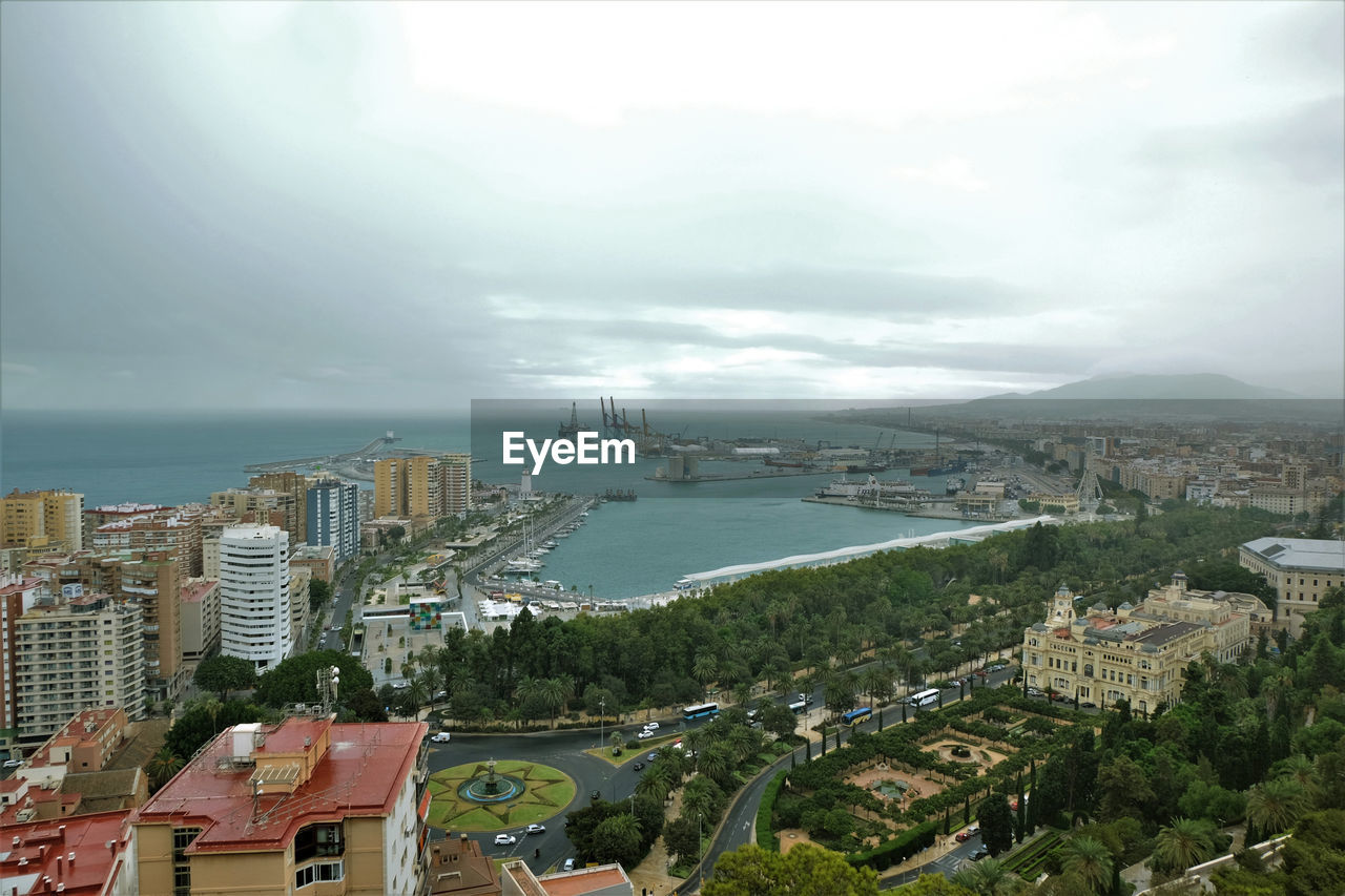 HIGH ANGLE VIEW OF CITYSCAPE AND SEA AGAINST SKY