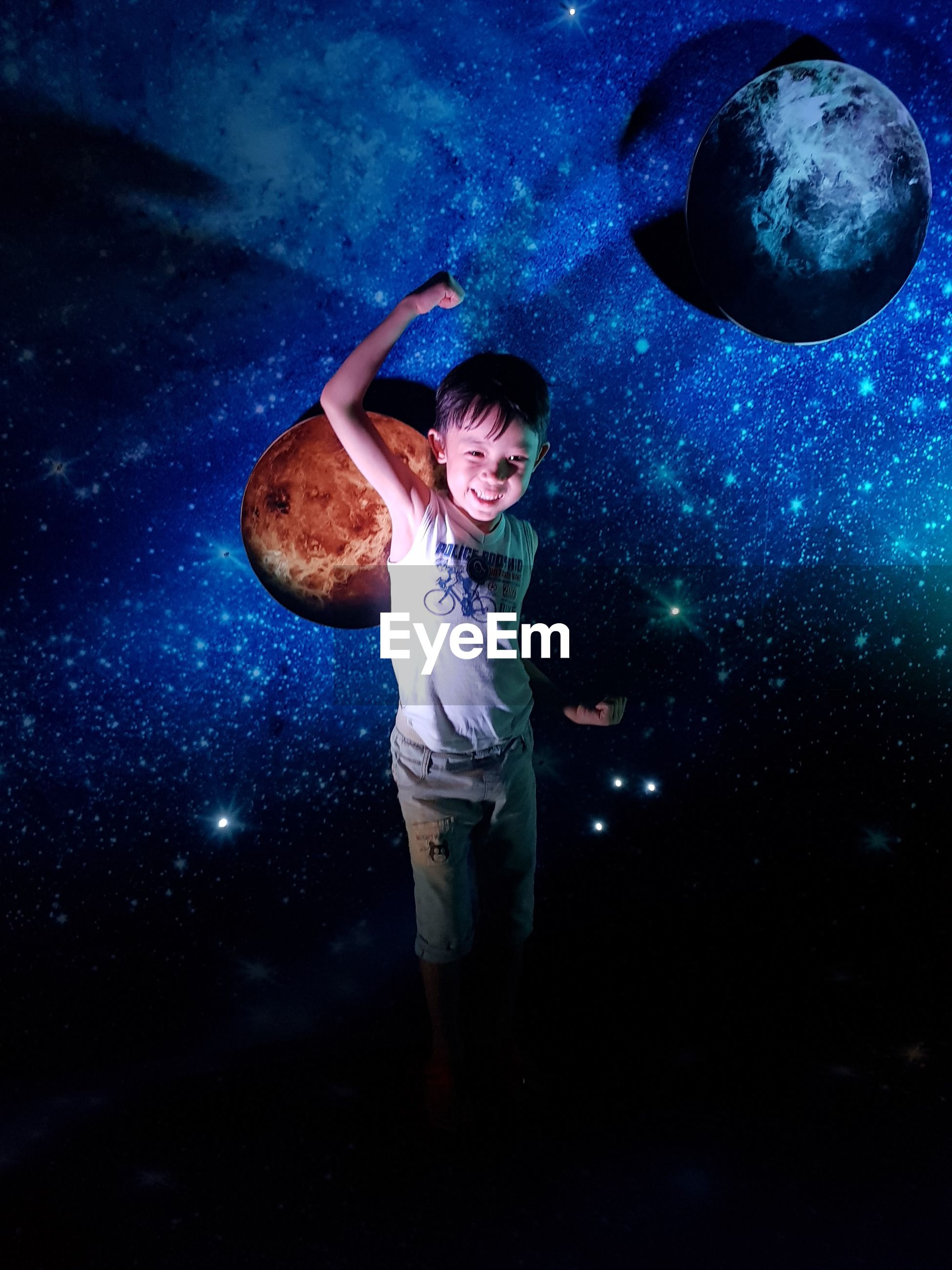 Digital composite image of boy standing against star field at night