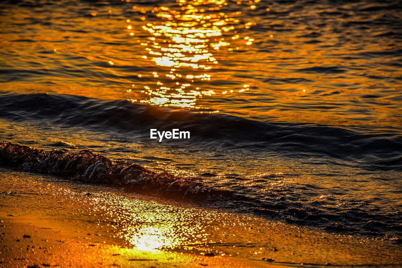 water, sunset, beauty in nature, nature, reflection, sunlight, no people, orange color, sea, sky, tranquility, motion, scenics - nature, waterfront, outdoors, land, wave, rippled