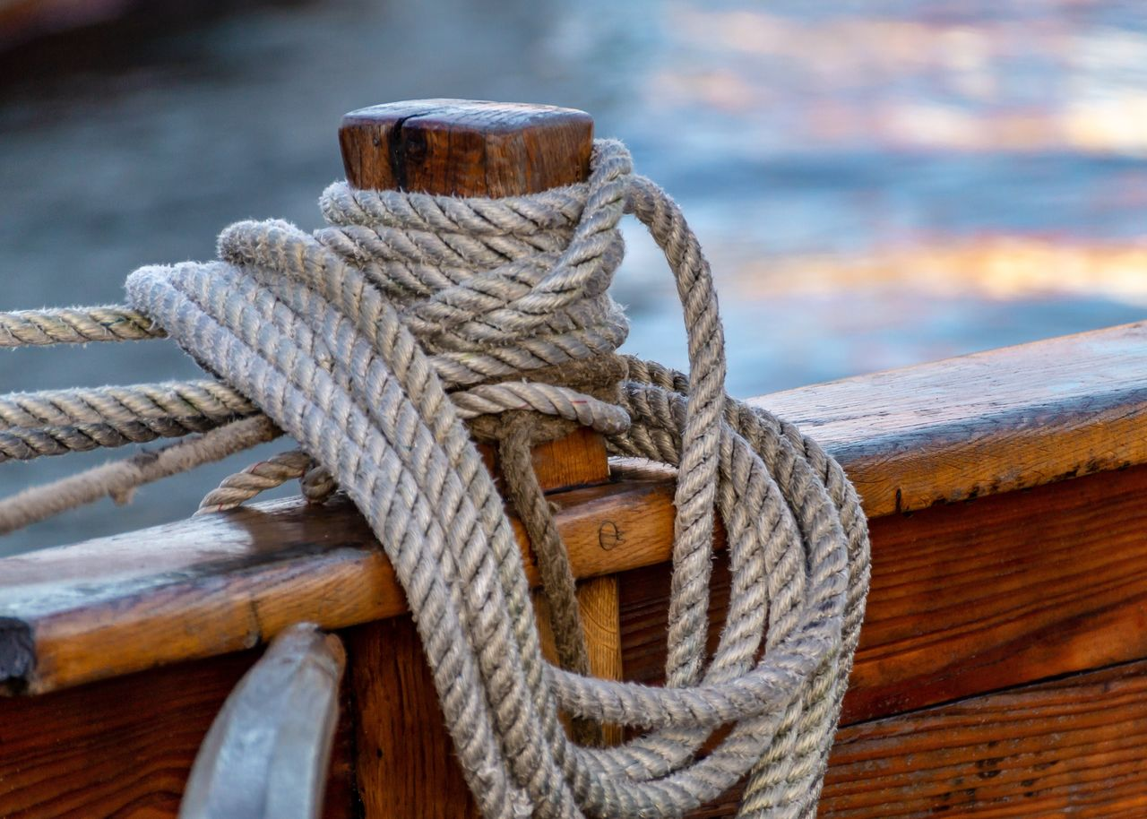 rope, strength, nautical vessel, tied up, transportation, water, mode of transportation, focus on foreground, close-up, wood - material, day, no people, post, outdoors, cleat, connection, nature, moored, tied knot, sea, wooden post, sailboat