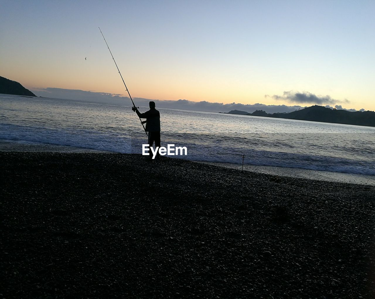 fishing, sea, fishing rod, silhouette, sunset, fishing pole, water, standing, tranquil scene, real people, full length, one person, beauty in nature, nature, weekend activities, scenics, leisure activity, tranquility, holding, beach, fishing tackle, horizon over water, men, outdoors, sky, lifestyles, vacations, clear sky, day, adult, people