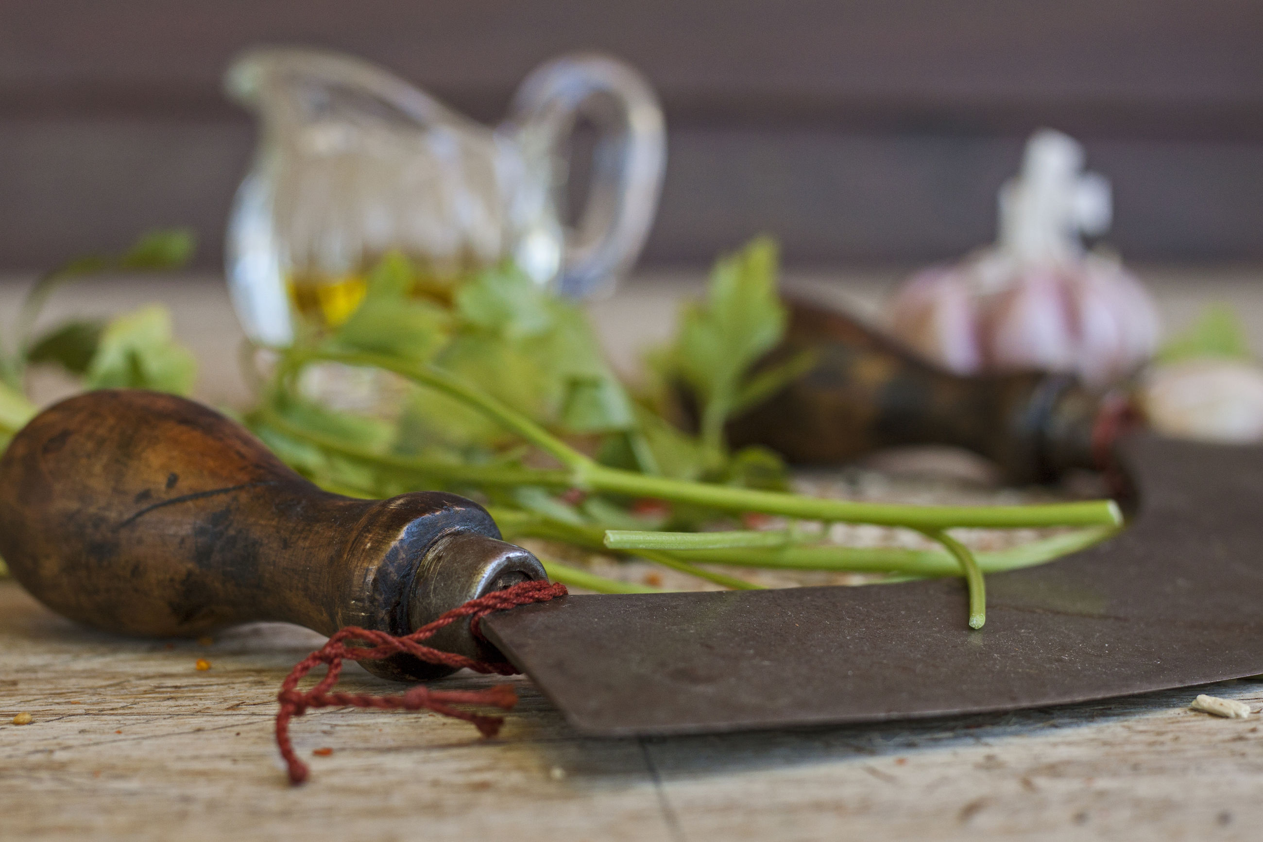 Close-up of mincing knife by cilantro leaves and spice on table