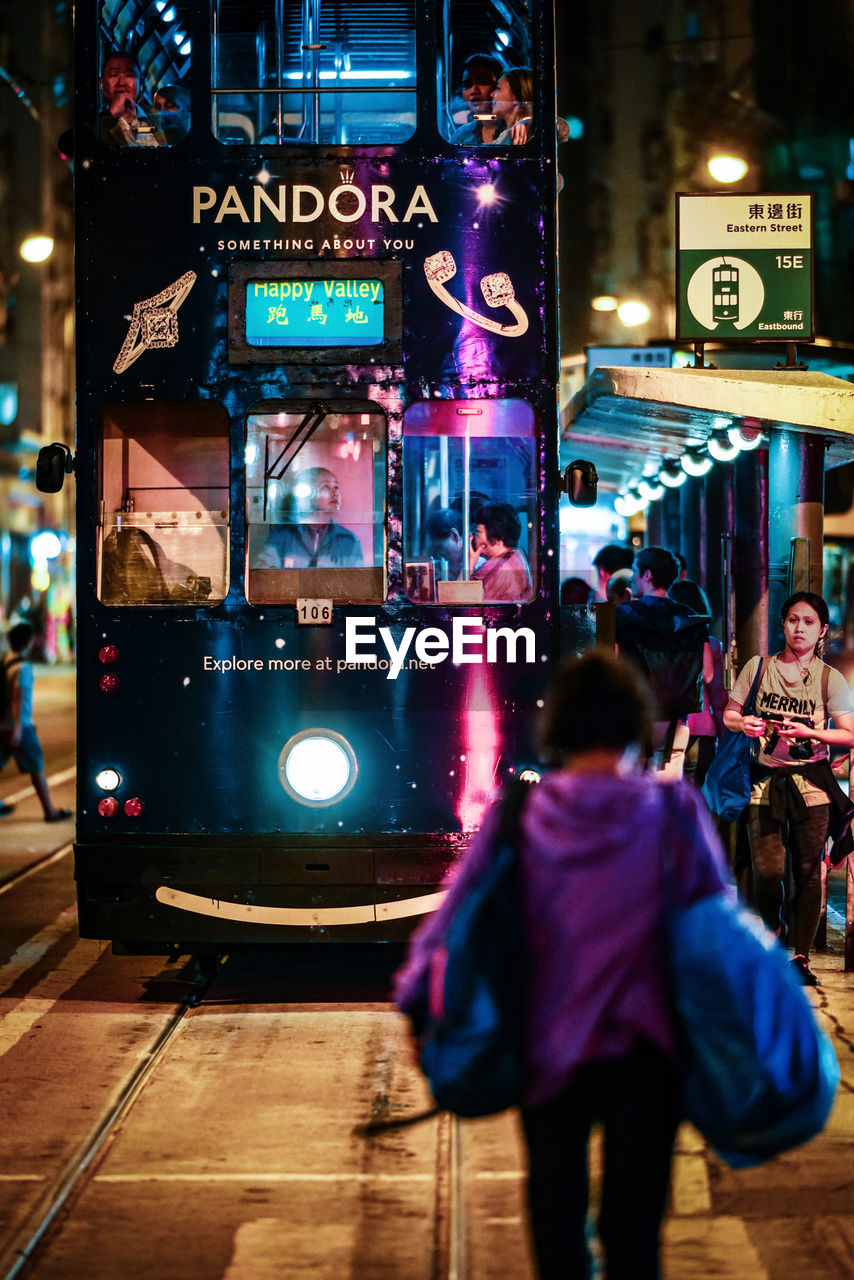 city, illuminated, night, real people, street, city life, architecture, incidental people, rear view, walking, building exterior, one person, built structure, lifestyles, leisure activity, transportation, women, mode of transportation, lighting equipment, nightlife