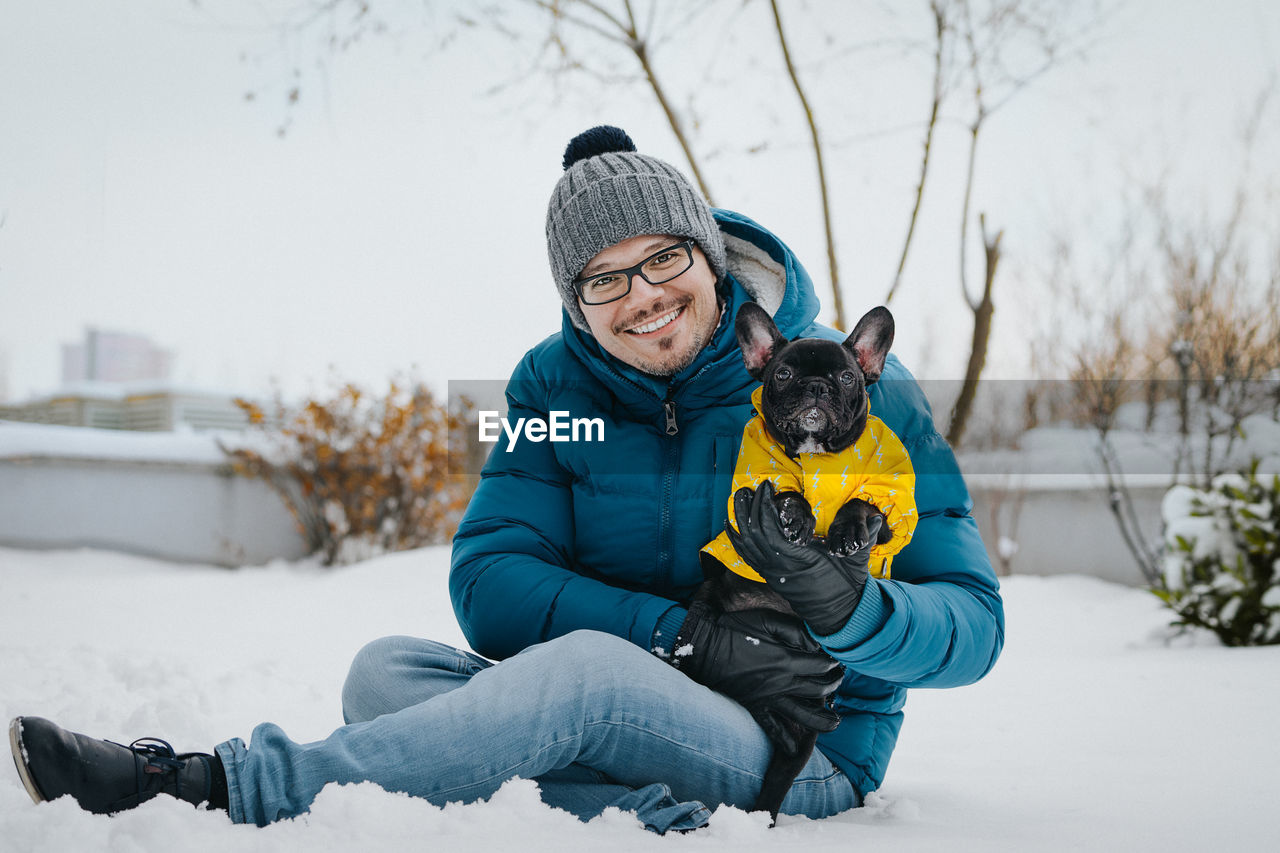 Portrait Of Man With Dog Sitting On Snow Covered Field
