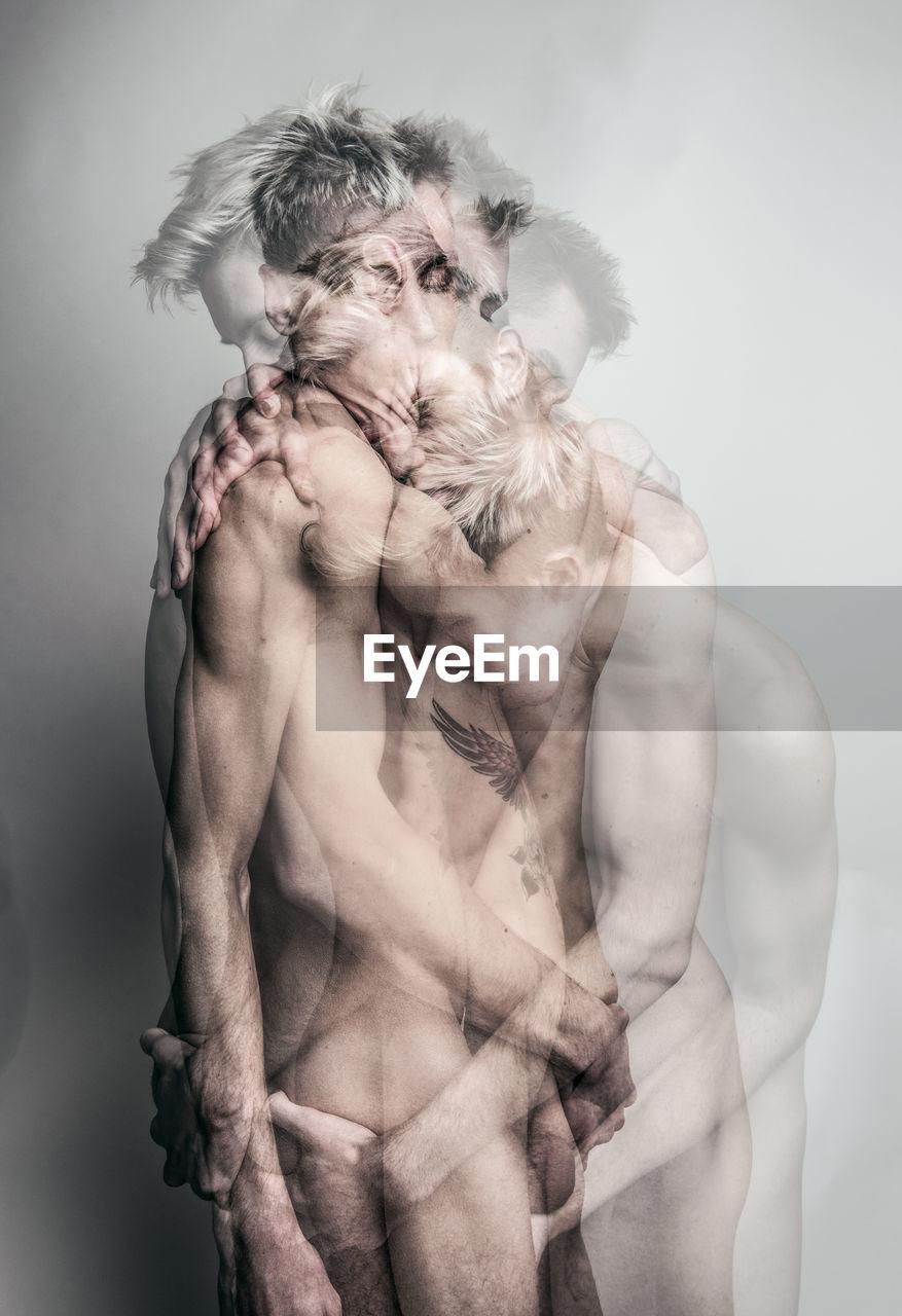 Digital Composite Image Of Shirtless Gay Men Embracing Against Gray Background