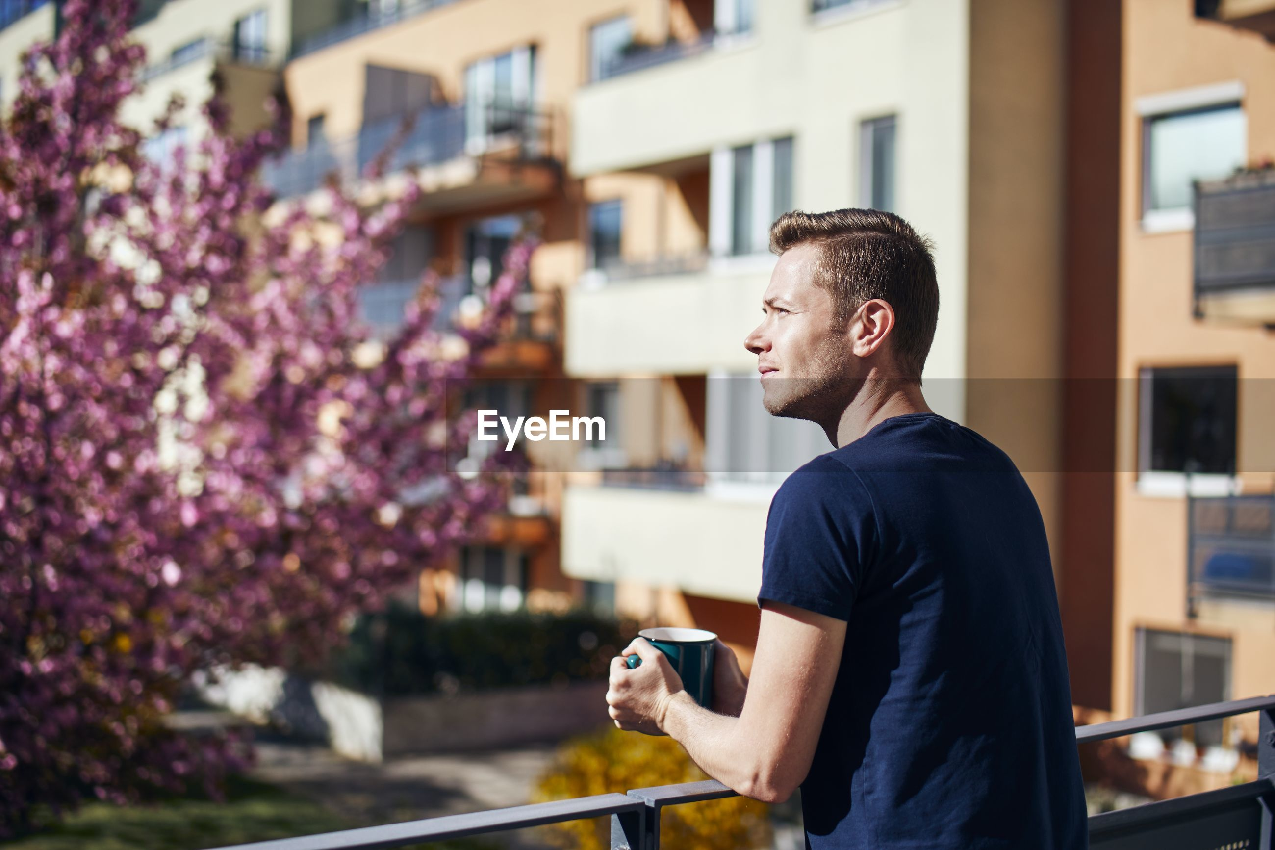 Man having coffee while standing at balcony