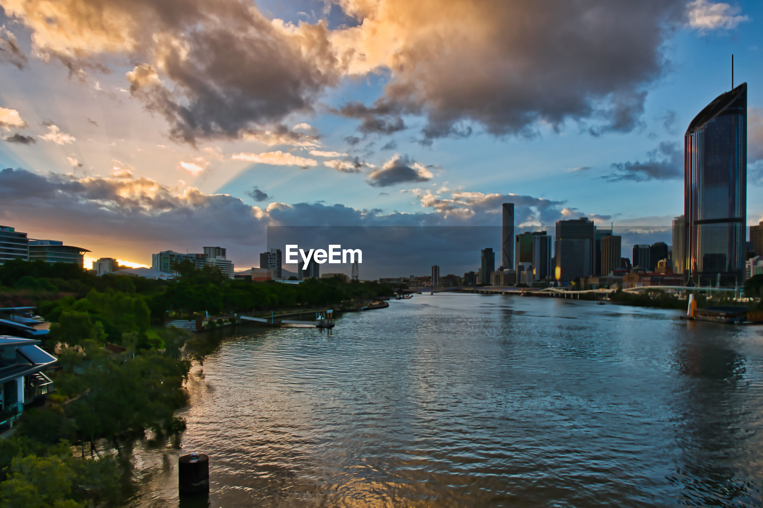 RIVER BY BUILDINGS AGAINST SKY DURING SUNSET