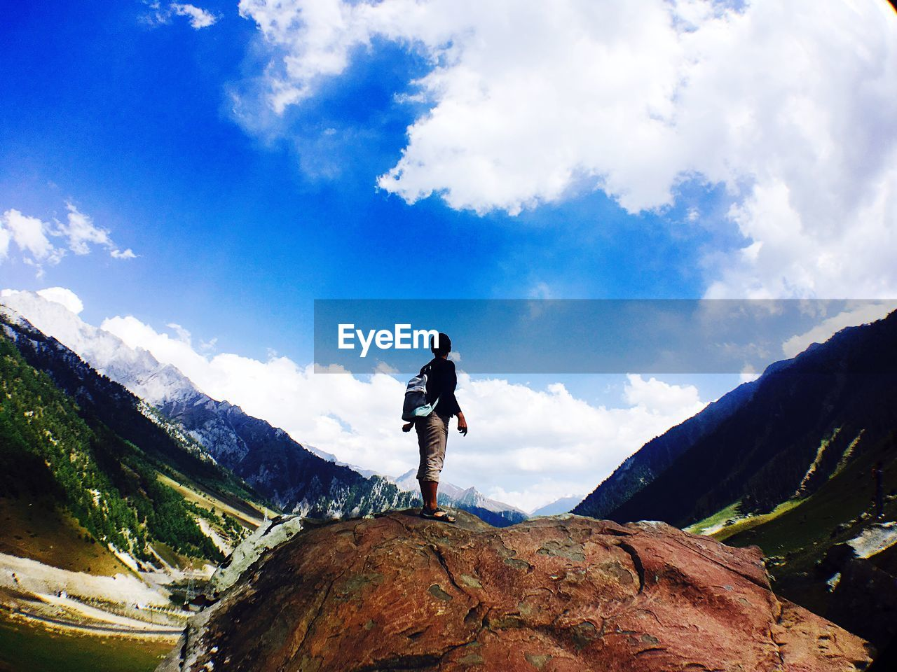 cloud - sky, sky, mountain, rock - object, scenics, nature, beauty in nature, adventure, full length, tranquility, standing, one person, real people, tranquil scene, day, exploration, hiking, landscape, low angle view, leisure activity, outdoors, men, mountain range, blue, lifestyles, vacations, peak, people