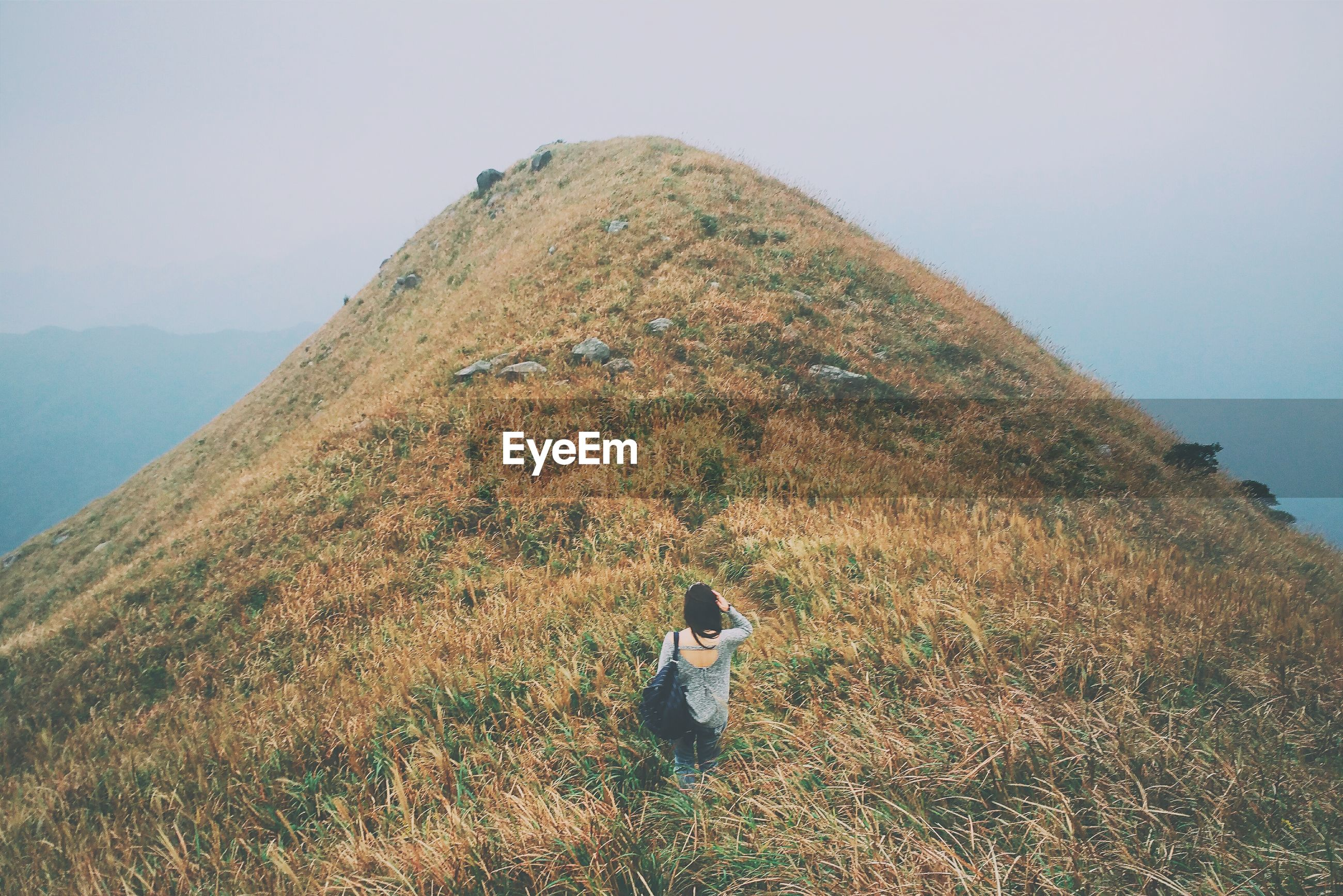 High angle view of woman standing on mountain against sky during foggy weather