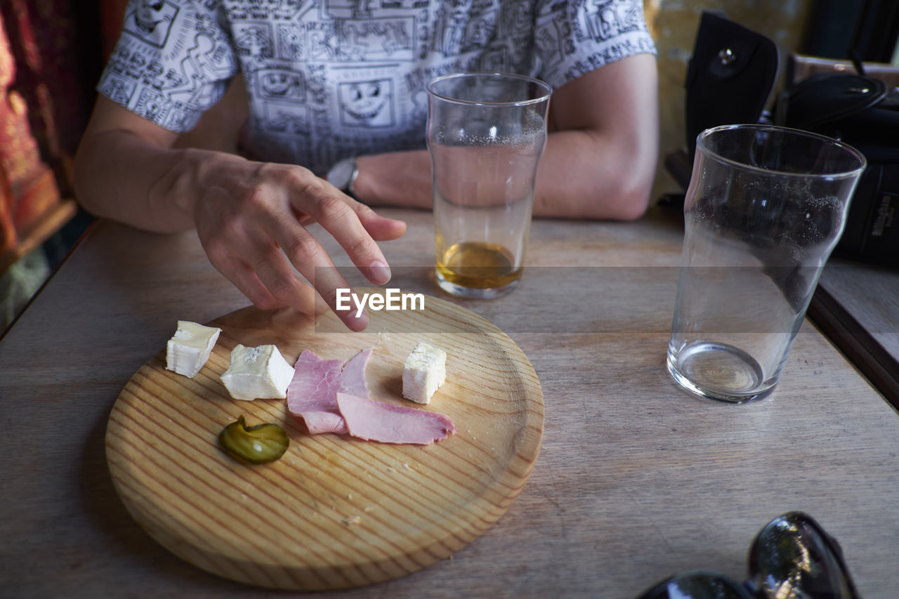 food and drink, indoors, one person, real people, table, glass, food, midsection, alcohol, freshness, human hand, hand, drink, holding, refreshment, drinking glass, household equipment, wood - material, lifestyles