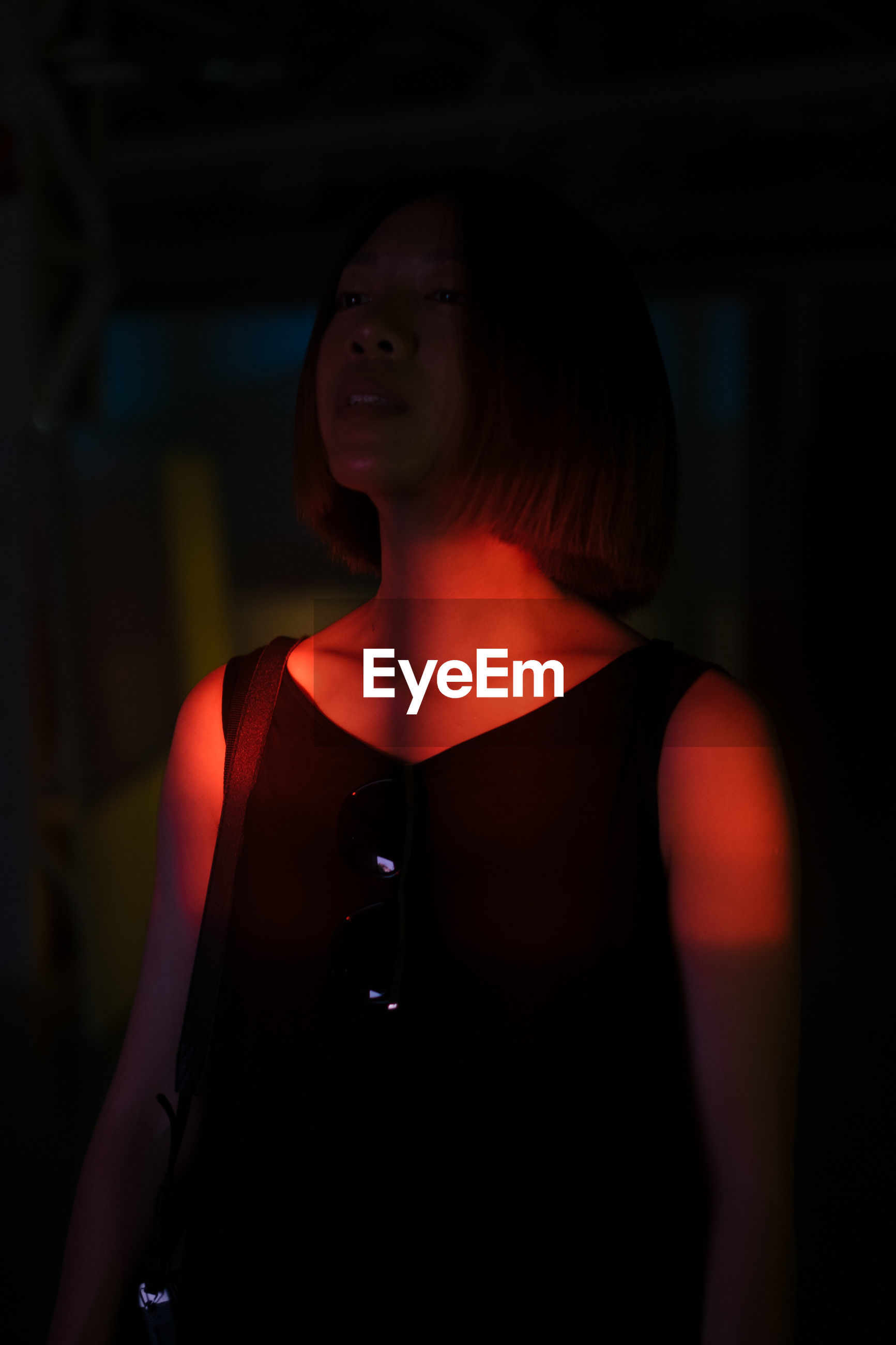 Thoughtful woman standing in darkroom