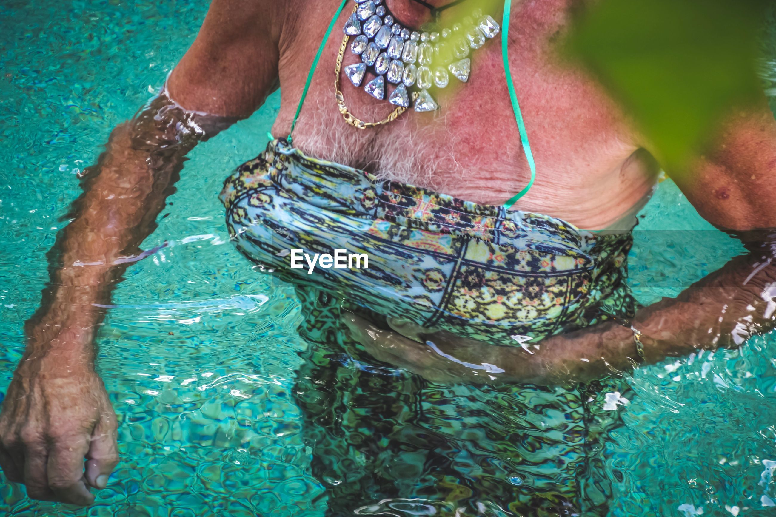 Midsection of senior woman swimming in pool