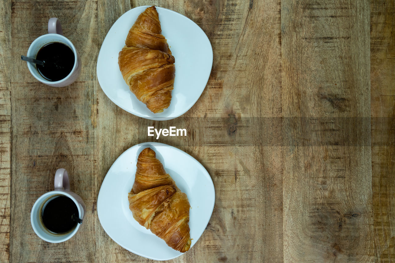 food and drink, table, coffee, cup, drink, coffee - drink, freshness, food, refreshment, directly above, baked, coffee cup, mug, breakfast, indoors, plate, meal, still life, croissant, wood - material, french food, no people, crockery, snack, tea cup