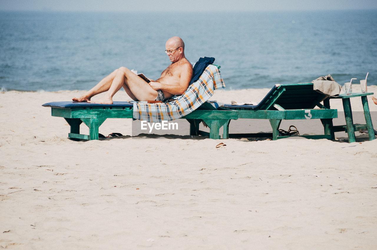 MAN SITTING ON BEACH AGAINST SEA