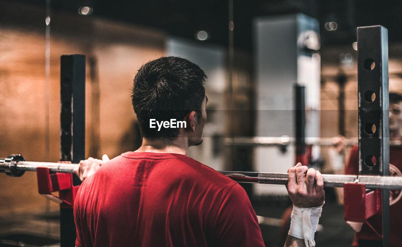 Rear view of man lifting barbell at gym