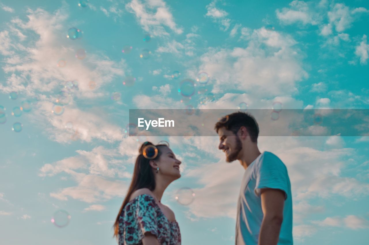 Low angle view of smiling young couple standing against cloudy sky