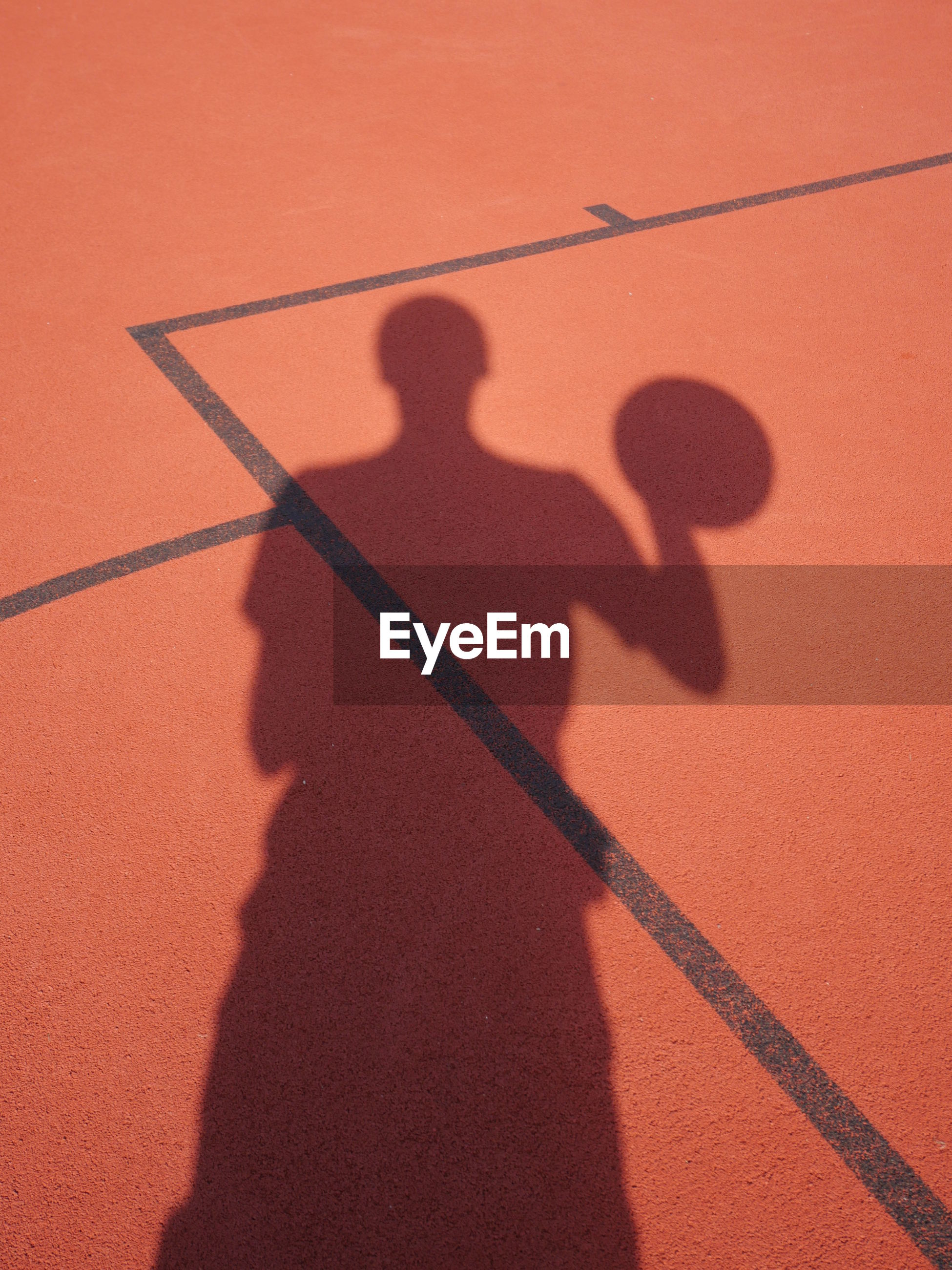 Shadow of player on basket ball court