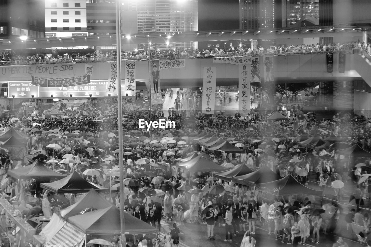 glass - material, transparent, indoors, illuminated, adult, retail, crowd, store, women, large group of objects, real people, choice, arrangement, for sale, large group of people, window, group of people, food and drink