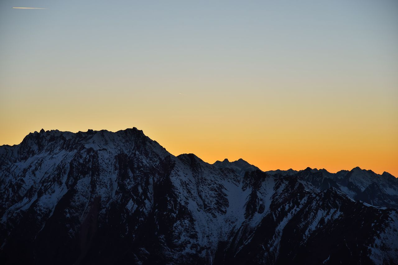sky, beauty in nature, sunset, mountain, scenics - nature, tranquil scene, tranquility, cold temperature, clear sky, nature, winter, mountain range, snow, non-urban scene, idyllic, environment, orange color, no people, copy space, mountain peak, outdoors, snowcapped mountain, formation