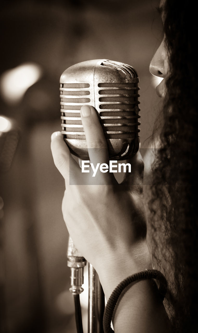 Close-up of woman singing over microphone