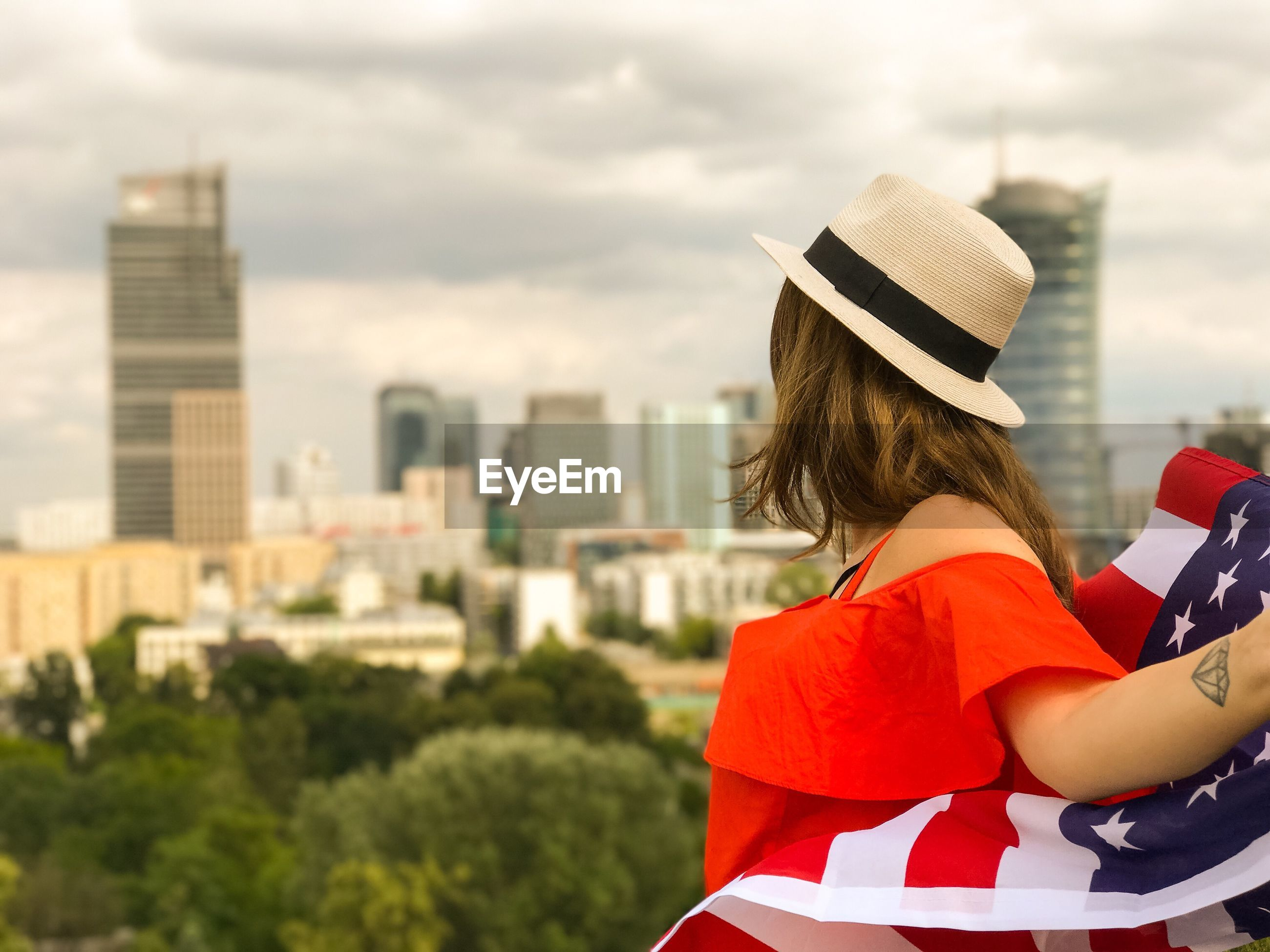Side view of mid adult woman with american flag in city standing against cloudy sky