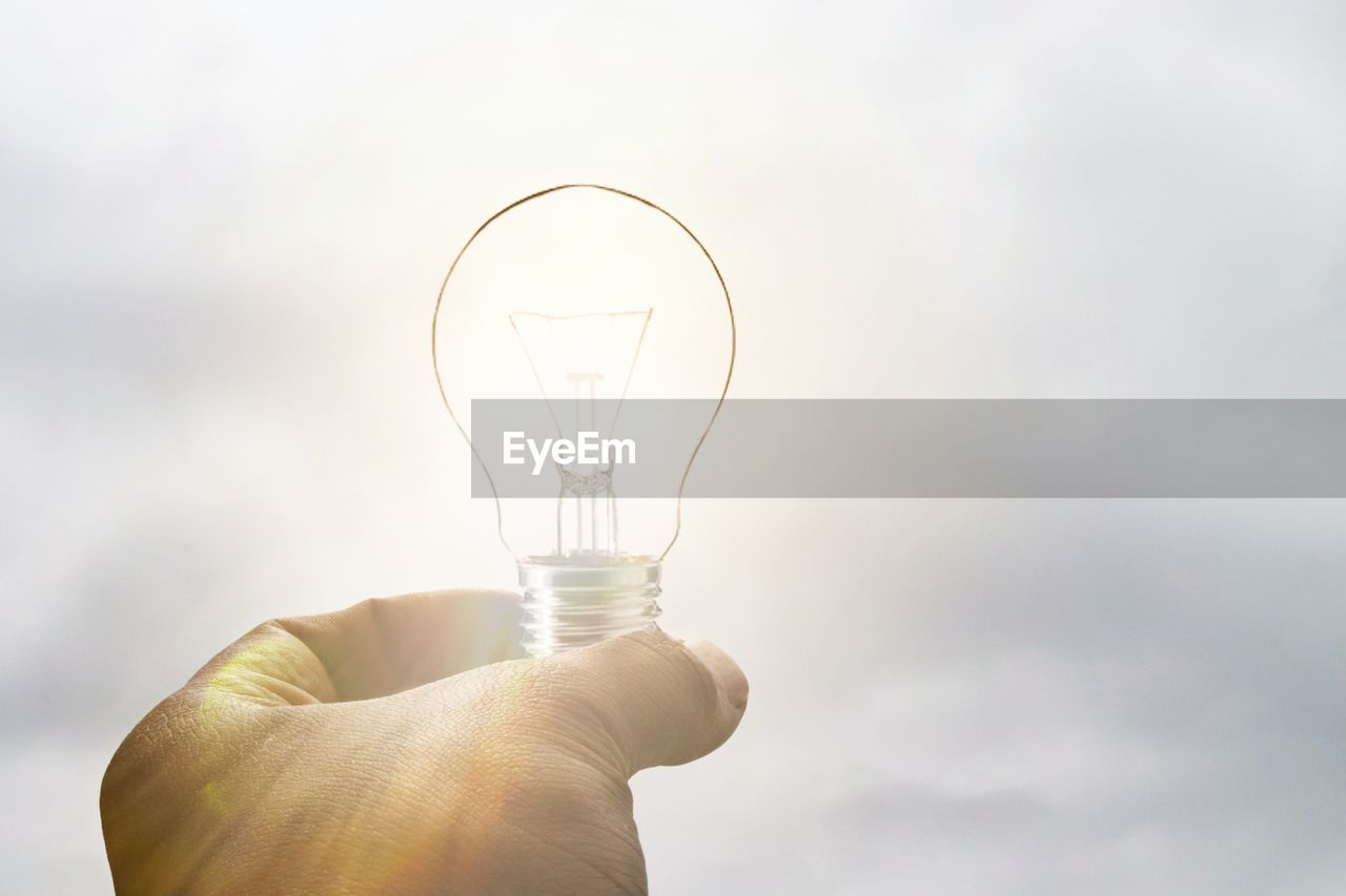 light bulb, human body part, human hand, hand, lighting equipment, one person, electricity, holding, glass - material, finger, unrecognizable person, body part, transparent, human finger, fuel and power generation, close-up, filament, sky, real people, technology, power supply, light, glass