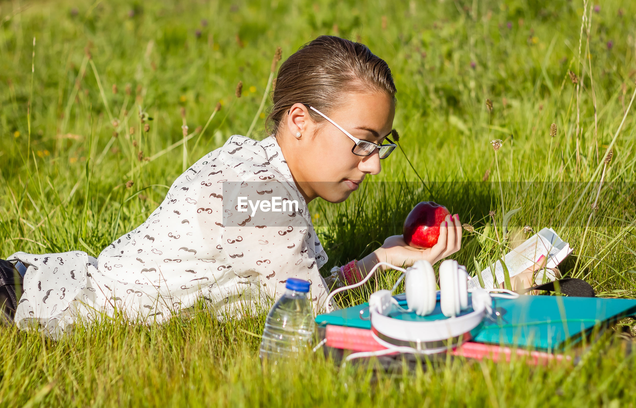 Young woman reading book while lying on grass at park
