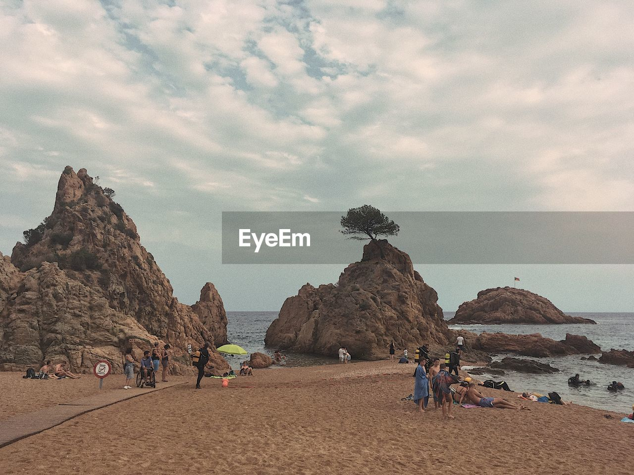 sky, cloud - sky, beach, nature, sand, real people, large group of people, rock formation, sea, rock - object, lifestyles, leisure activity, beauty in nature, scenics, outdoors, day, walking, men, women, mountain, vacations, water, people
