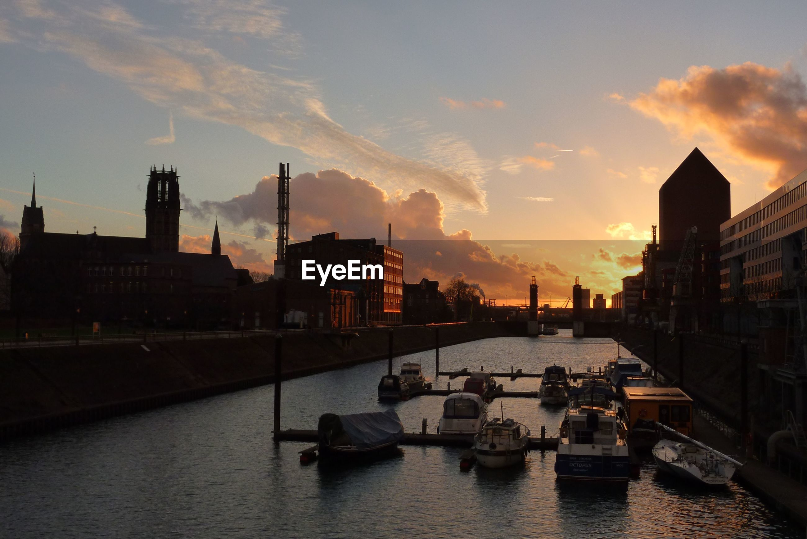 Boats on river against sky during sunset in city
