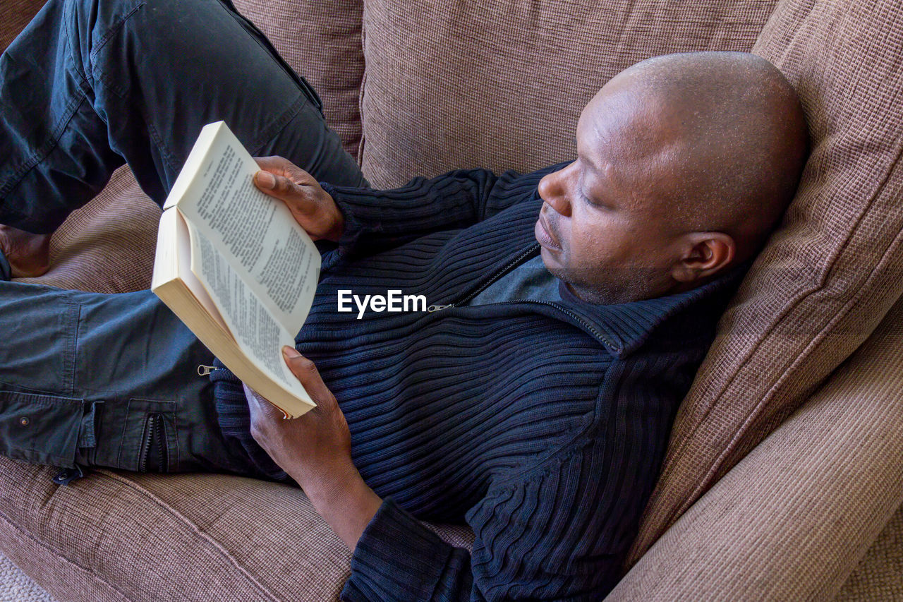 High angle view of man reading book while lying on sofa at home