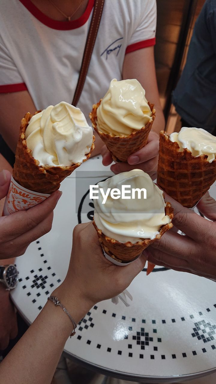 food and drink, food, holding, human hand, hand, freshness, indulgence, sweet, dessert, sweet food, real people, frozen, ice cream, unhealthy eating, temptation, midsection, human body part, two people, dairy product, lifestyles