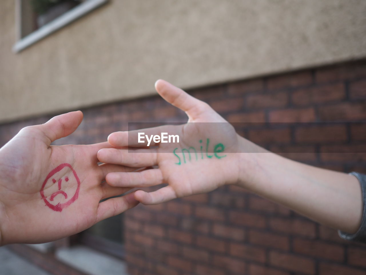 Cropped Hands With Anthropomorphic Face And Text On Palms Against Building