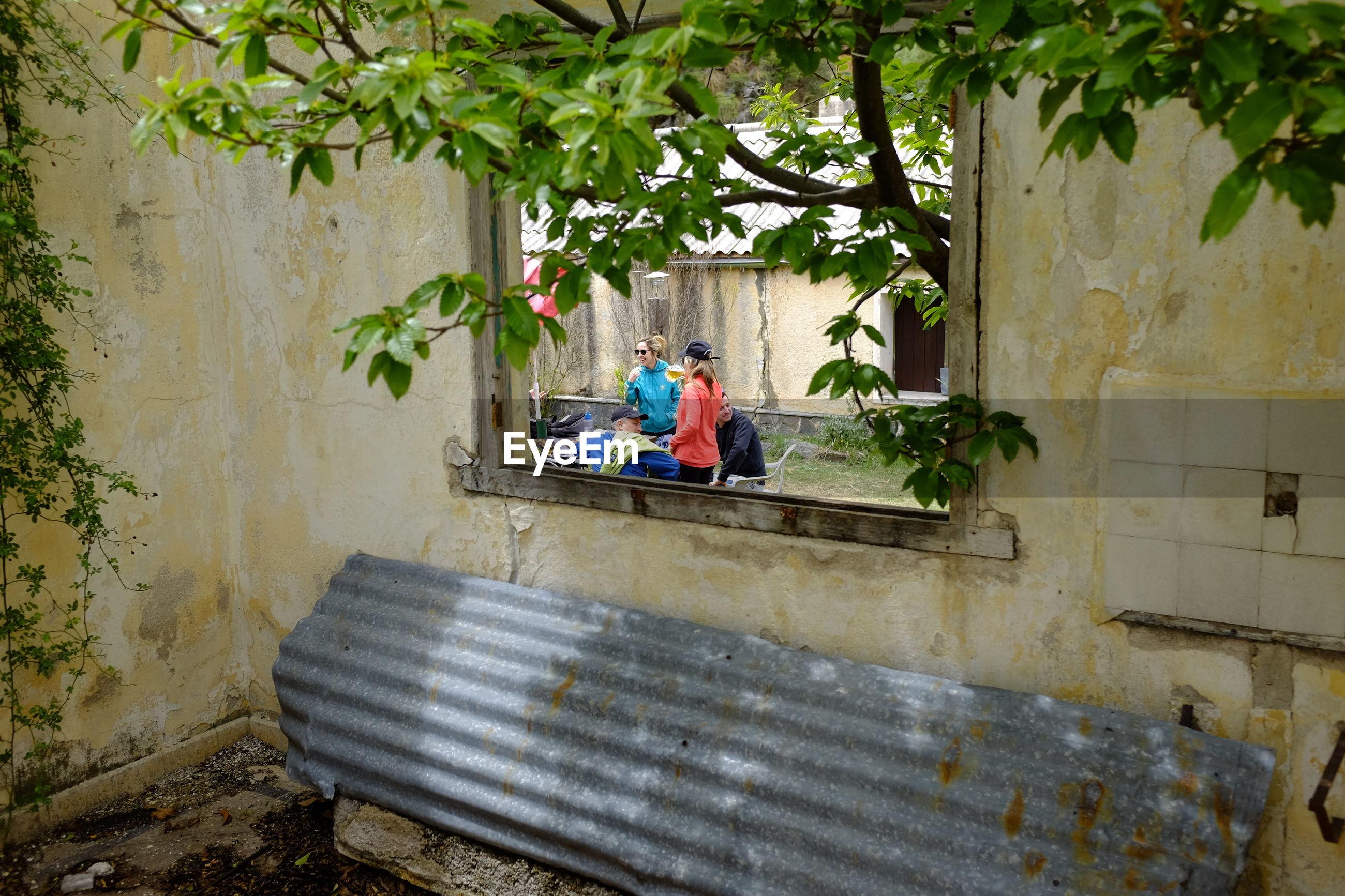 People on land seen through window