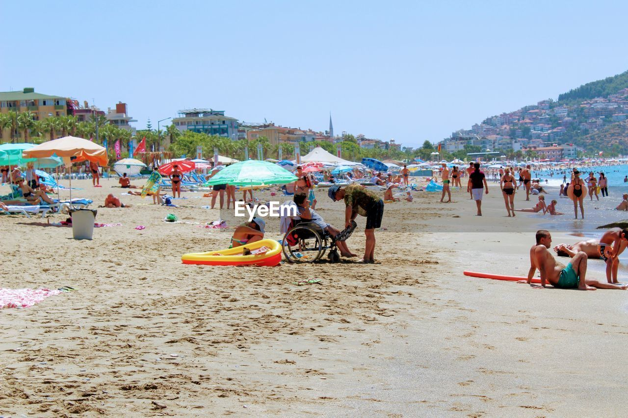 beach, large group of people, sand, vacations, real people, enjoyment, shore, summer, day, outdoors, men, fun, leisure activity, nature, lifestyles, clear sky, women, water, sky, people, adult